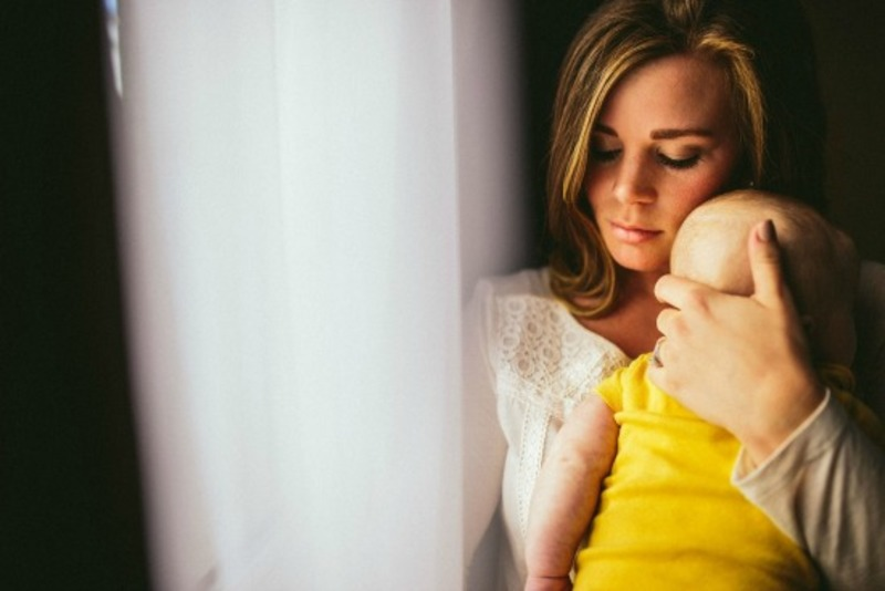 A mother who looks reflective gently cradles her baby  - Post-natal depression more distinct from other mood disorders than realised